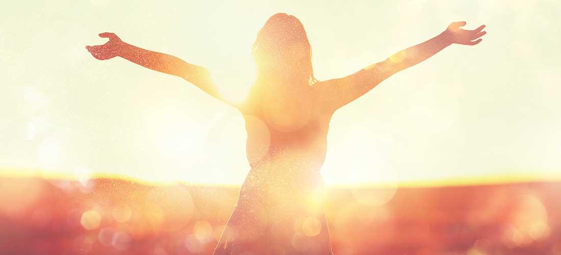 Frau glücklich bei Sonnenuntergang