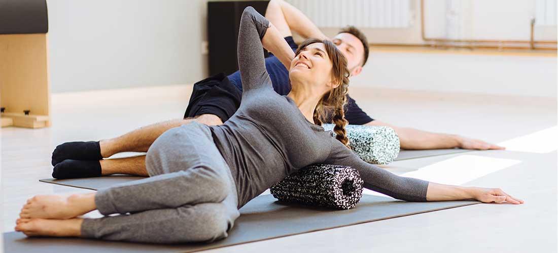 Frau und Mann trainieren mit der Faszienrolle
